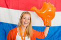 Sports fan wearing an inflatable orange hand cheering in front o portrait of happy young dutch standing of the flag of the Royalty Free Stock Photography