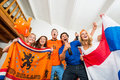 Sports fans excitement excited young multiethnic soccer in dutch national colors with tension and joy written on their faces Royalty Free Stock Images