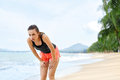 Sports fitness fit woman taking break after running workout athletic resting jogging tired exhausted female runner a breathing Royalty Free Stock Image