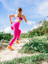 Sports girl running in mountains. Fitness on nature Royalty Free Stock Photo