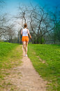 Sports girl runs in park Royalty Free Stock Image