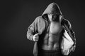 Sports guy in a tracksuit man jacket with hood the takes off her jacket and shows his muscular body fitness Royalty Free Stock Images