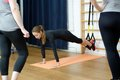 Sports instructor shows how to do exercise on suspension rope trx group of girls