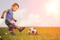 Sports kid. Boy playing football. Baby with ball on sports field Royalty Free Stock Photo