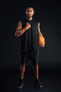 Sports man with basket ball holding hand on his chest Royalty Free Stock Photo
