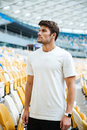 Sports man standing at the stadium outdoors and looking aside. Royalty Free Stock Photo