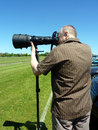 Sports photographer a with large telephoto zoom lens to get close to the action Royalty Free Stock Photography