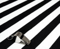 Sports referee whistle on jersey stripes Stock Photography