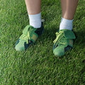 Sports shoes feet of woman dressed in green on grass Royalty Free Stock Photo
