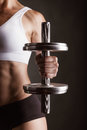 Sports woman close up dumbbell in hand on a dark background Royalty Free Stock Photo