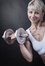 Sports woman fitness with dumbbells on a dark background Stock Photography