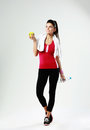 Sports woman holding yellow apple and bottle of water young thoughtful on gray background Royalty Free Stock Image