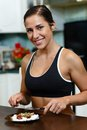 Sports woman and nutritional supplements young in sportswear sits in the house kitchen before plate with Stock Photos