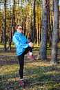 Sports young girl woman in the blue jacket exercising on the forest Royalty Free Stock Photography