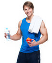 Sportsman in blue shirt holds water and apple portrait of handsome happy over white background Royalty Free Stock Image