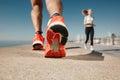 Sportsman fitness sunrise jog workout welness concept runner feet running on road closeup on shoe Royalty Free Stock Photo