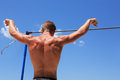 Sportsman before high bar young strong athlete standing horizontal against blue sky Stock Images