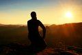 Sportsman hiker in black sportswear sit on mountain top and take a rest tourist watch down to morning misty valley sportsmann with Stock Images
