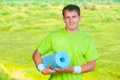 A sportsman holding yoga mat young in sports clothes on nature Royalty Free Stock Photos