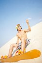 Sportsman on sand young with sandboard sitting beach Stock Images
