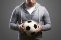 Sportsman with soccer ball young holding a studio shot on gray background Royalty Free Stock Photo