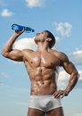 Sportsman the very muscular handsome sexy guy on sky background drink water focus on face Royalty Free Stock Photography