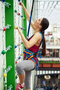 Sportswoman is climbing on the wall with chains in rock climbing safety equipment indoor center Stock Photos
