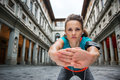 Sportswoman with headset is stretching next to Uffizi gallery Royalty Free Stock Photo