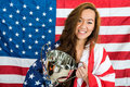 Sportswoman holding trophy against north american flag portrait of happy young while standing Royalty Free Stock Images