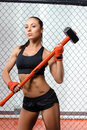 Sportswoman with a hummer in gym shocking strength young beautiful woman holding fighting cage Stock Images
