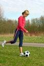Sportswoman Kicking a Ball Royalty Free Stock Photo