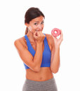 Sporty adult woman holding tempting food in sport clothing sugary against white background Royalty Free Stock Photo