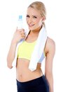 Sporty blond woman posing with water bottle and white towel around her neck Royalty Free Stock Photos