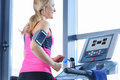 Sporty blonde woman exercising on treadmill in gym Royalty Free Stock Photo