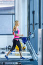 Sporty blonde woman exercising on treadmill Royalty Free Stock Photo