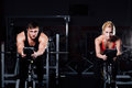Sporty couple exercising at the fitness the exercise bike on a dark  gym. Royalty Free Stock Photo