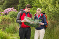 Sporty couple on a hike looking at map in the countryside Royalty Free Stock Photos