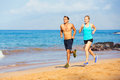Sporty couple jogging together on the beach athletic Stock Images