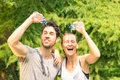 Sporty couple refreshing with cold water after run training in the park sport fitness young happy models taking a break Royalty Free Stock Image