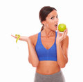 Sporty female eating apple to keep fit woman and against white background Royalty Free Stock Images