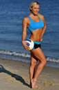 A sporty fit woman in her fitness clothes holding a volleyball ball on the beach Stock Photography