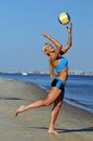 A sporty fit woman in her fitness clothes playing volleyball on the beach Royalty Free Stock Images