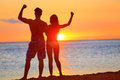 Sporty fitness couple cheering at beach sunset happy romantic fit young enjoying with arms raised up flexing muscles Royalty Free Stock Image