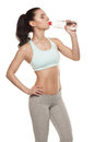Sporty girl drinking water from a bottle after a workout, fitness training, isolated on white background Royalty Free Stock Photo