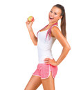 Sporty girl holding an apple while standing sideways Stock Images
