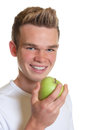 Sporty guy eating an apple smiling with blond her eats on white background Stock Photography