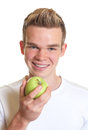 Sporty guy showing an apple attractive with blond hair loves apples Royalty Free Stock Photo