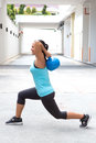 Sporty hispanic woman in blue demostrating a routine with blue kettlebell outdoors beautiful Royalty Free Stock Photo