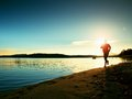 Sporty man doing morning jogging on sea beach at bright sunrise silhouettes running sportsman Royalty Free Stock Image