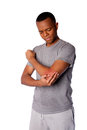 Sporty man with painful sports injury on elbow in gray shirt and sweatpants isolated Royalty Free Stock Photos